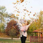 Mama mit Baby in LIMAS Babytrage Rosa Beige mit Herbstblättern